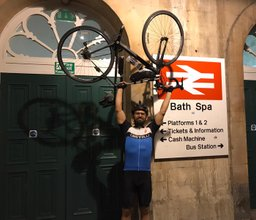 Bisher Diyani lifting his bike as he arrives in Bath